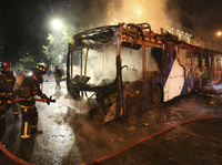 Firefighters put out the flames on a burning bus during a protest against the rising cost of subway and bus fares in Santiago, Chile.