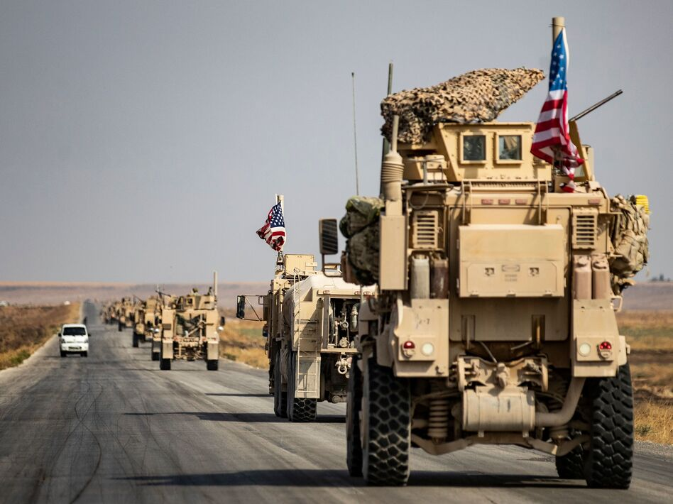 U.S. military vehicles drive on a road in the town of Tal Tamr on Sunday after pulling out of a base in northern Syria. Defense Secretary Mark Esper says some troops may remain in northeast Syria to secure oil fields. (Delil Souleiman/AFP via Getty Images)