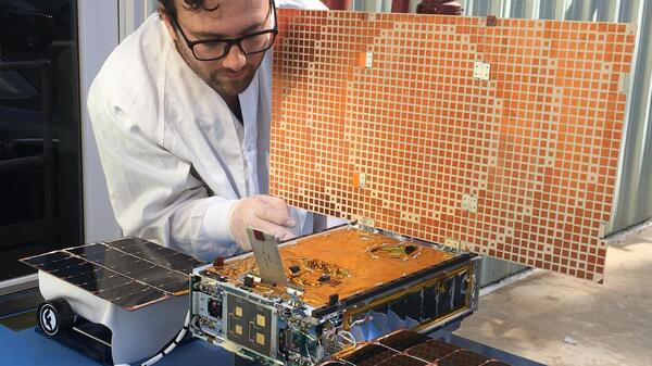 Engineer Joel Steinkraus tests solar panels on one of two CubeSats that made up NASA