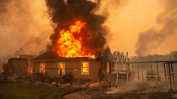 A home burns at a vineyard during the Kincade fire near Geyserville, Calif., on Thursday.