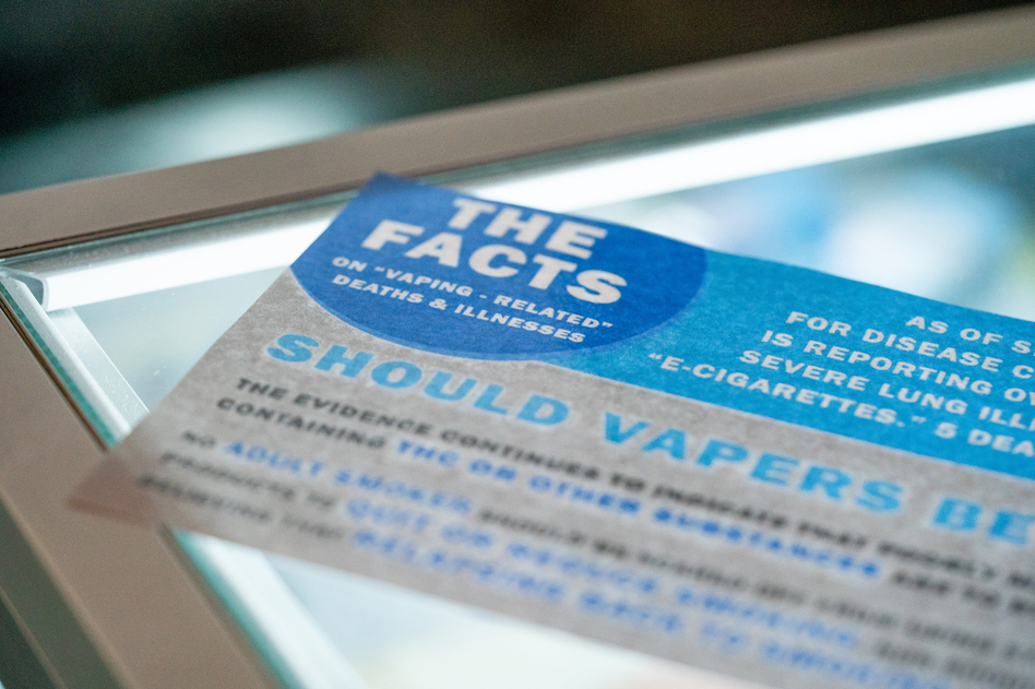 A flyer reminding customers about vaping-related deaths and illnesses, on display in a Seattle vape store. The Washington State Board of Health recently passed a four-month emergency ban on flavored vaping products. It applies to products that contain either THC or nicotine. (Jovelle Tamayo/Bloomberg/Getty Images)
