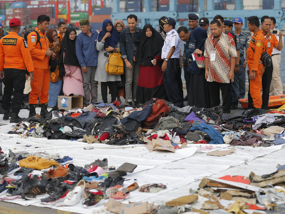 Relatives of passengers of the crashed Lion Air jet check personal belongings retrieved from the waters where the airplane crashed, at Tanjung Priok Port in Jakarta, Indonesia, last October. (Tatan Syuflana/AP)