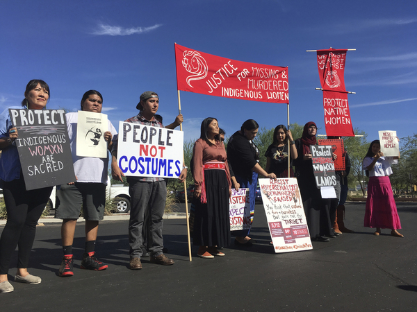 "Native American protesters stand outside the Phoenix office of Yandy.com, a retailer of ""sexy Native American"" costumes on Oct. 24, 2018. For some ethnic and racial groups, Halloween has long been haunted by costumes that perpetuate stereotypes and instances of cultural appropriation."
