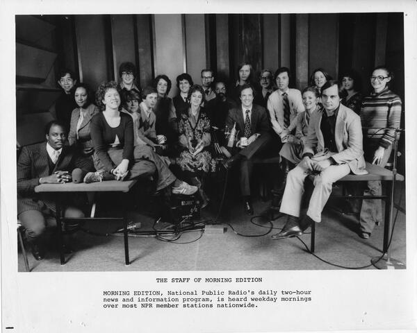 A staff photo taken during the early days of Morning Edition. Co-host Bob Edwards is in the back row, standing seventh from the left among the three men in glasses. His co-host, Barbara Hoctor, sits in the front, fourth from the left, between the two men holding mugs. Hoctor left the show after a few weeks. Edwards was host until 2004, when he went to SiriusXM.