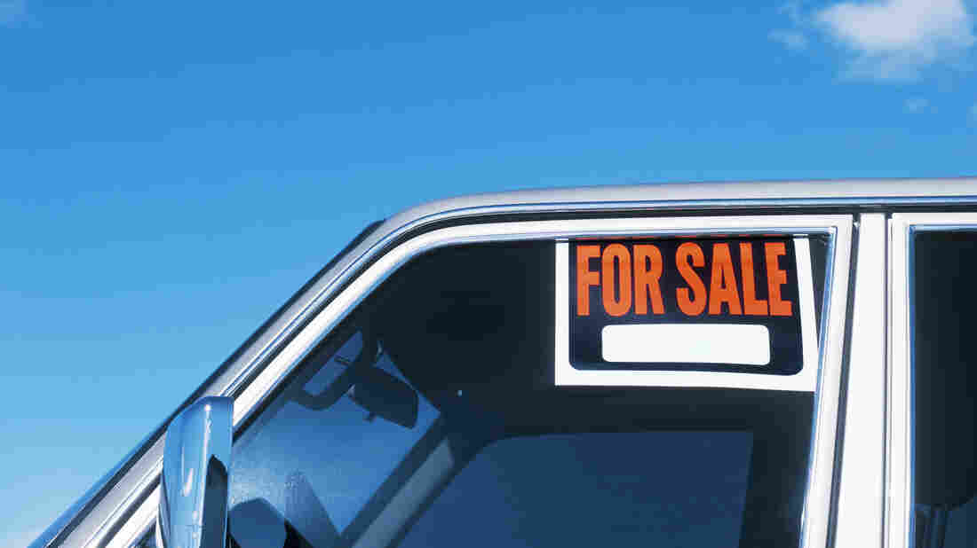 A For Sale sign is displayed on the window of a car.