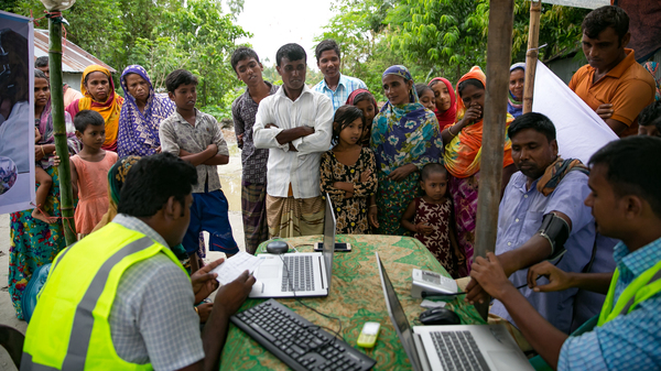 Patients line up for remote health consultation sessions on a char near Rangpur, Bangladesh.