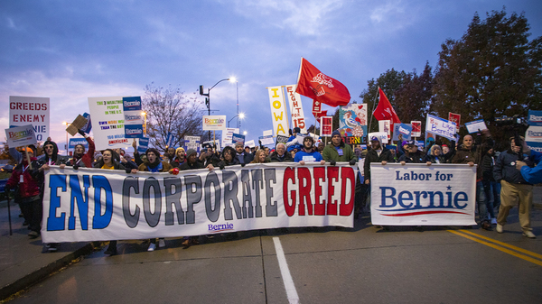 Supporters of Vermont Sen. Bernie Sanders march in Des Moines outside the Iowa Democratic Party's Liberty and Justice Celebration.