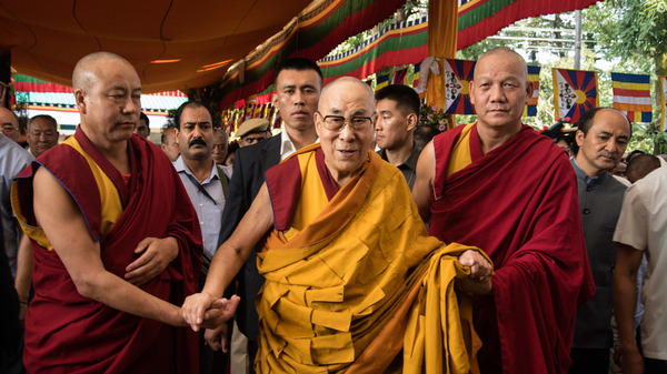 Flanked by Buddhist monks, the Dalai Lama, 84, greets visitors in September at a prayer ceremony at his monastery in Dharamsala, India.
