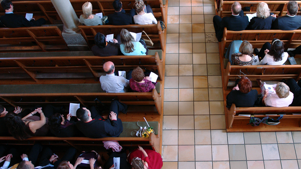People sitting in the pews of a house of worship.