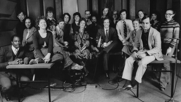 A staff photo taken during the early days of Morning Edition. Co-host Bob Edwards is in the back row, standing seventh from the left among the three men in glasses. His co-host, Barbara Hoctor, sits on the table at right, holding a mug. Hoctor left the show after a few weeks. Edwards was host until 2004, when he went to SiriusXM.