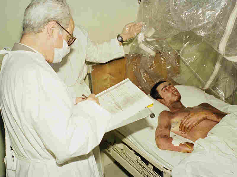 A United Nations representative takes notes while visiting an unidentified chemical warfare victim at Logman Hospital in Tehran, March 31, 1988. UN representatives visited victims of the Iraqi gas attack on the border town of Halabja in which thousands of Kurds were killed and injured.