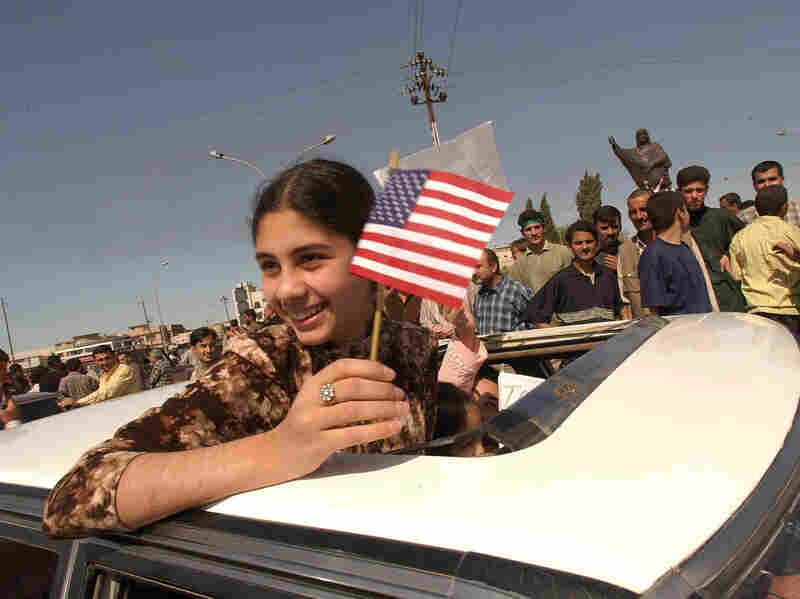 A Kurdish girl holds a U.S. flag during celebrations, April 10, 2003 in northern Iraq. Kurdish Peshmerga fighters and U.S. special operations soldiers took the city of Kirkuk amid little resistance.