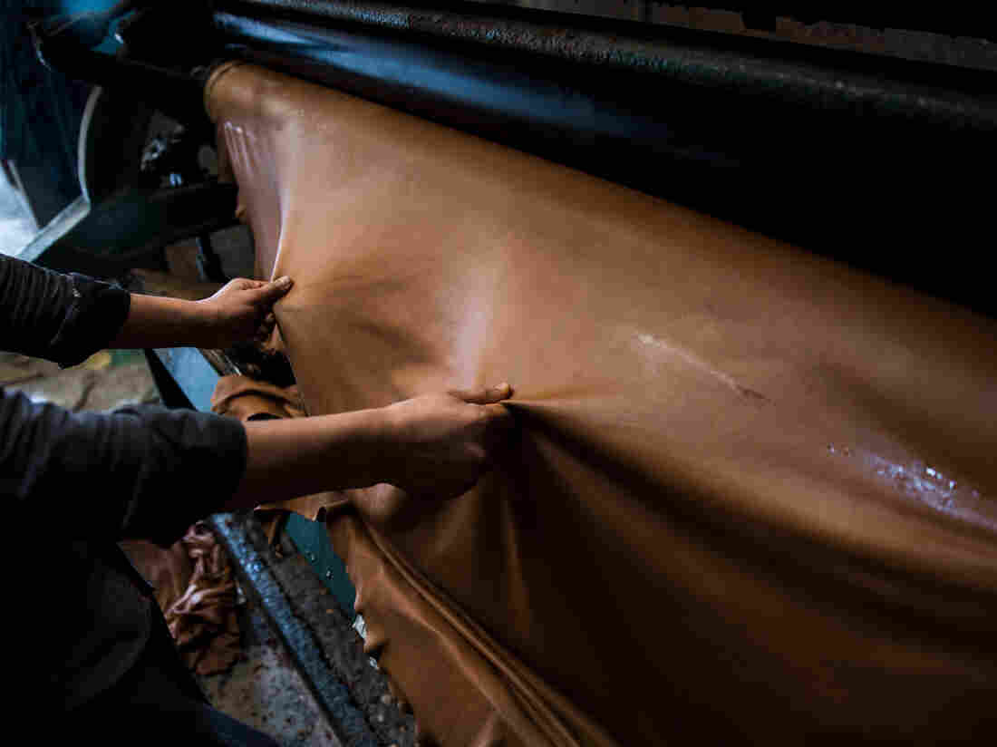 An employee handles a sheet of leather on a machine at a tannery in India. Photographer: Taylor Weidman/Bloomberg