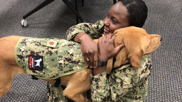 Brelahn Wyatt, a Navy ensign and second-year medical student, shares a hug with Shetland. The dog