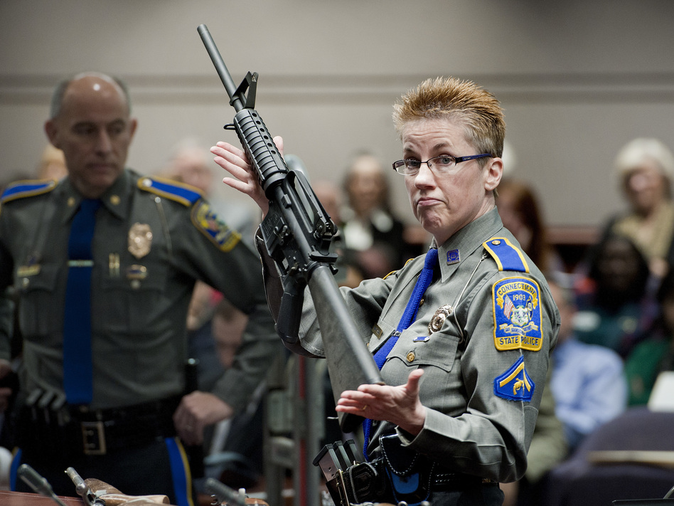 Connecticut State Police Detective Barbara J. Mattson holds a Bushmaster AR-15-style rifle, the same type of gun used in the Sandy Hook shooting, during a 2013 hearing in Hartford, Conn. The gun-maker Remington is being sued by the families of the victims. (Jessica Hill/AP)