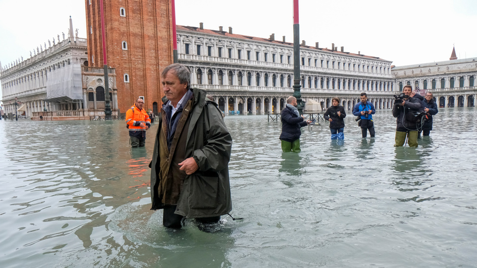Venice Mayor Luigi Brugnaro trudges through high water in St. Mark's Square on Wednesday, the result of an exceptionally high tide in the scenic Italian city. (Manuel Silvestri/Reuters)