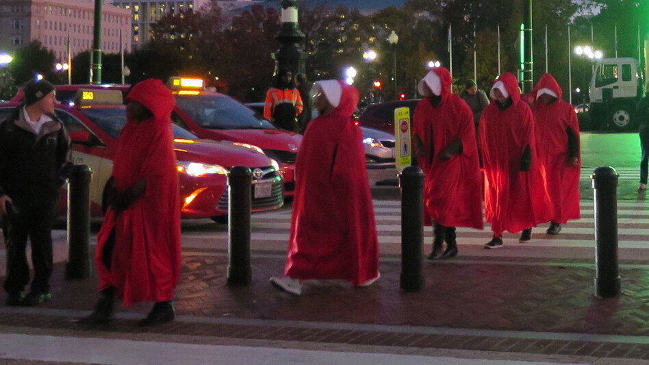 Protesters dressed as women from <em>The Handmaid's Tale</em> protest outside Justice Kavanaugh's speech. (Shontee Pant/NPR)