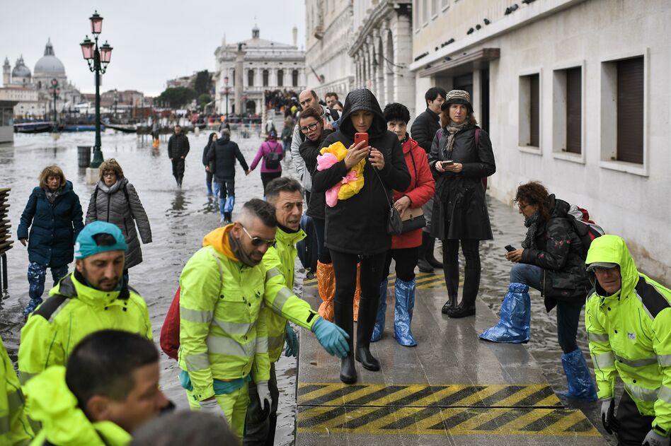 Volunteers set up a footbridge across Venice's flooded Riva degli Schiavoni embankment on Nov. 13. (Marco Bertorello / AFP via Getty Images)