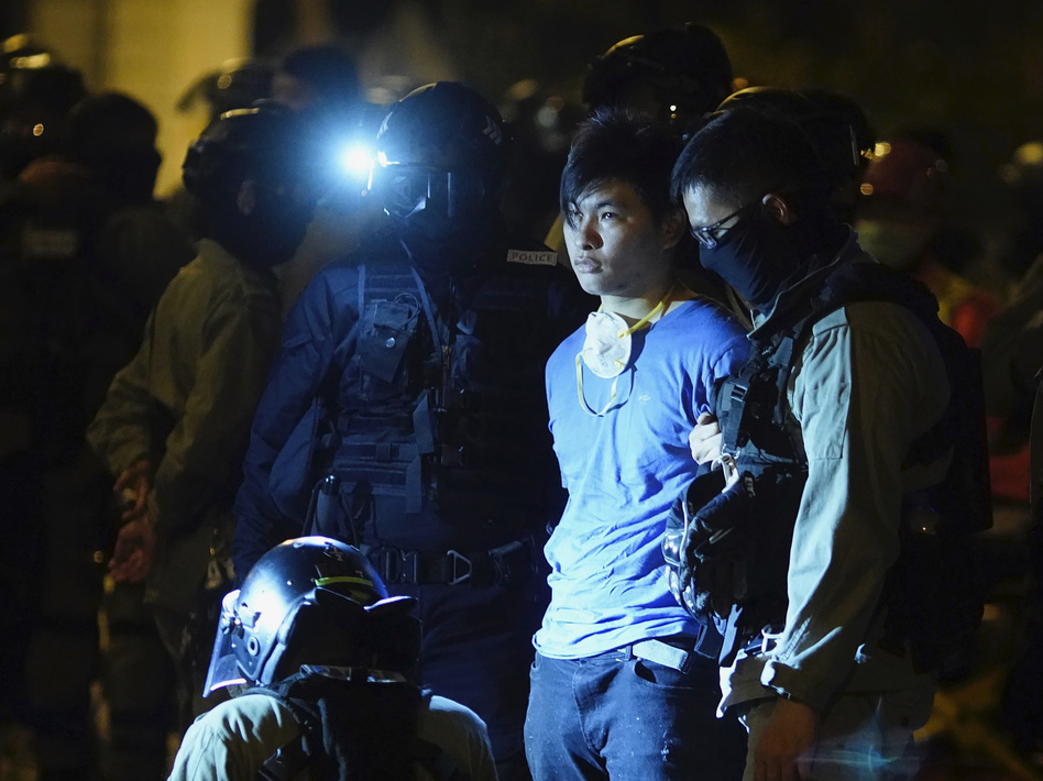 Riot police detain a protester on Tuesday near Hong Kong Polytechnic University, where  about 100 anti-government protesters remained holed up. (Vincent Yu/AP)