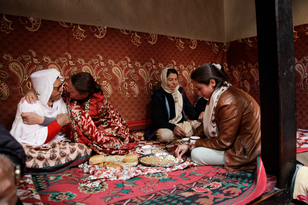 Gulmit residents sit around a brazier, used for heating and cooking, in a communal hall where they were celebrating a wedding.