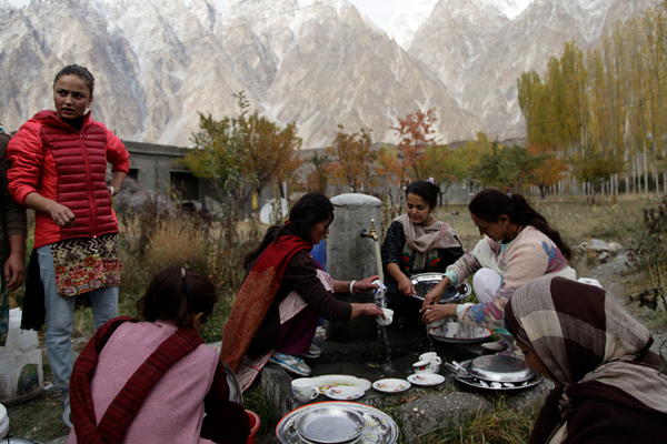 Women and girls wash dishes at a communal tap in the village of Passu, with the snow-capped Karakoram mountains in the background. The village relies on a nearby glacier — also called Passu — to water their fields, pastures and orchards. But the glacier is shrinking, and it is threatening the very existence of their village.