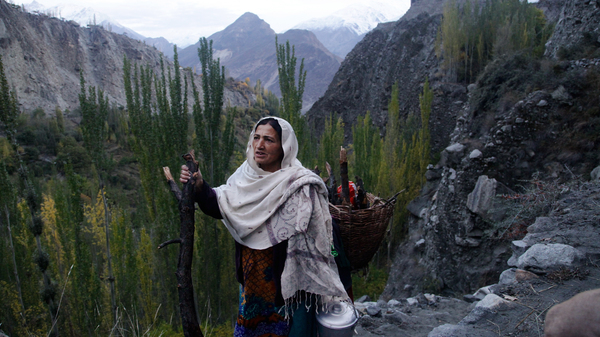 Shamim Banno, 55, walks up the Harchi Valley after she finished milking her cow. Farmers in the Harchi Valley in Pakistan