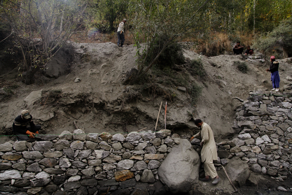 Workers build stone walls along parts of the riverbank in Harchi Valley, hoping that will prevent future glacial floods from washing away more land.