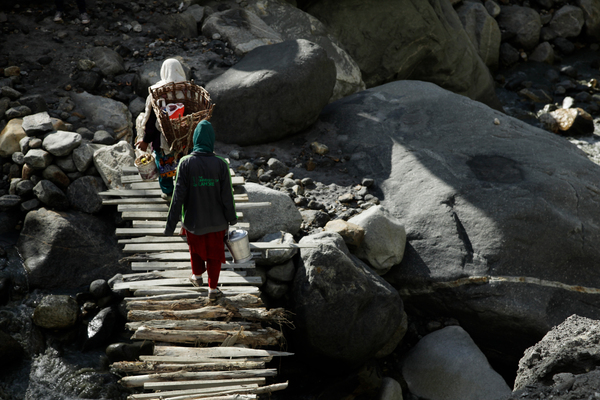 Residents cross a handmade wood-and-rope bridge over the river in the Harchi Valley. This is the fifth bridge that residents built this year, after the first four were washed away. They said that before this summer, a bridge usually lasted a decade.