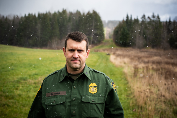 Richard Ross, patrol agent in charge of the United States Border Patrol's Newport Station, stands near the international boundary, marked by the slash in the forest, as snow falls.