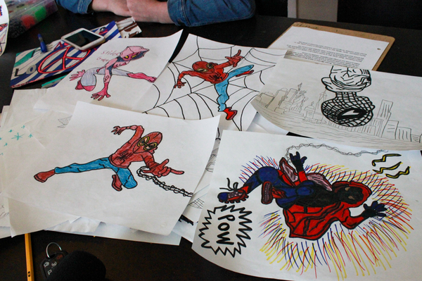 """Drawings made by Jenn and Jason's 15-year-old son lie on the family's dining room table in their home in central Illinois. Though his angry outbursts reveal a violent side, his parents say that most of the time he is """"kind, funny and smart"""" — a teen who enjoys drawing pictures of superheroes."""