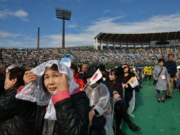 Attendees wait for a Holy Mass led by Pope Francis at a baseball stadium in Nagasaki on Sunday.