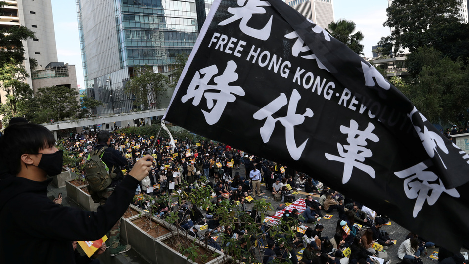 """China urges the U.S. to correct its mistake and stop meddling in Hong Kong affairs,"" a government spokesperson says, as China retaliates for U.S. support of pro-democracy demonstrators. Here, an activist holds a flag at a lunchtime protest Monday at Chater Garden in Hong Kong. (Leah Millis/Reuters)"