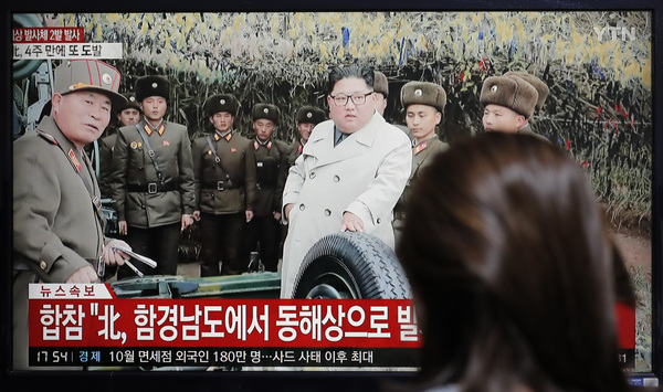 A woman watches a news program showing North Korean leader Kim Jong Un and reporting that North Korea firing unidentified projectiles last month.