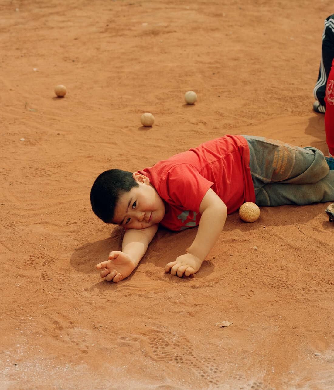 A boy lays on the baseball field