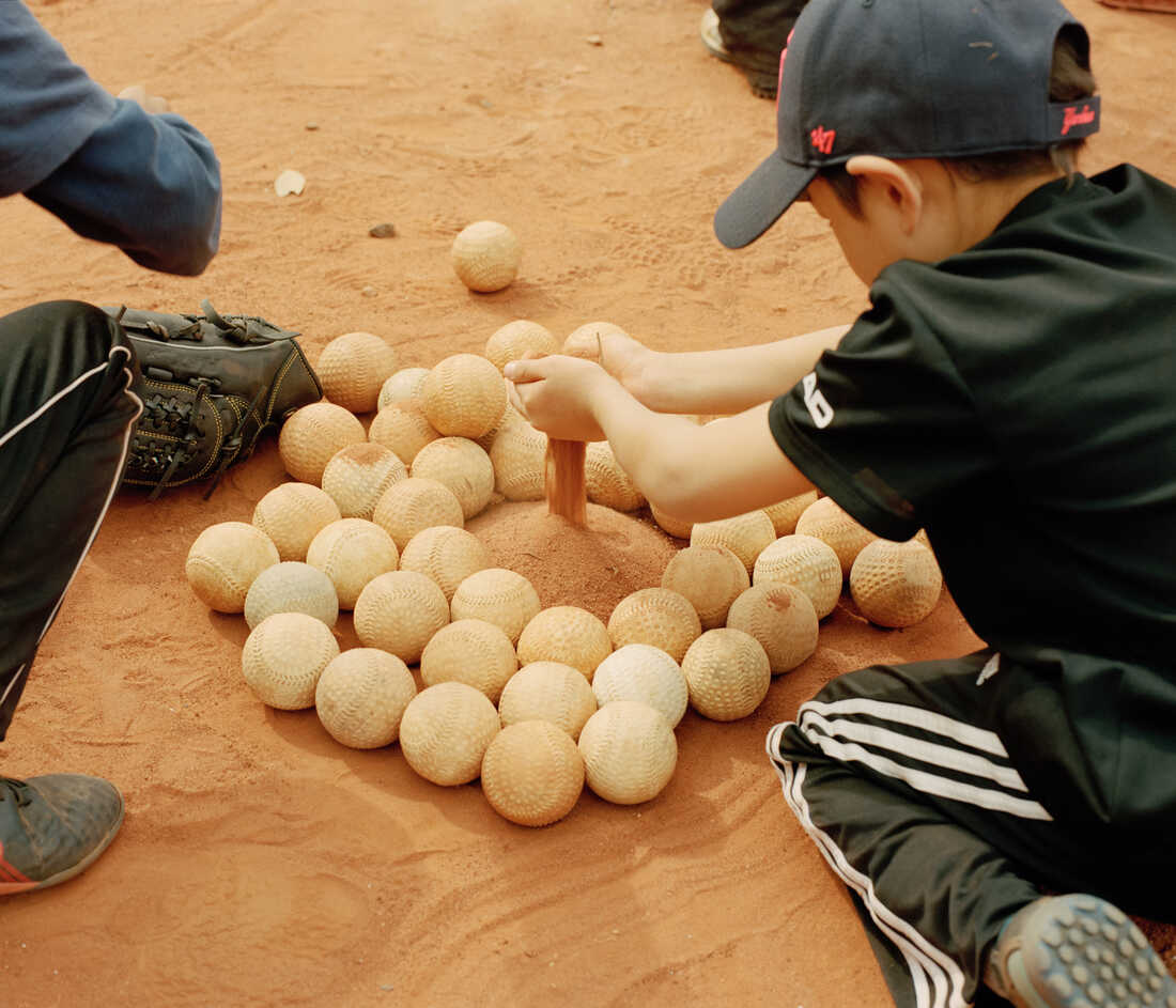 Children play in the sand of a baseball field next to a pile of baseballs.