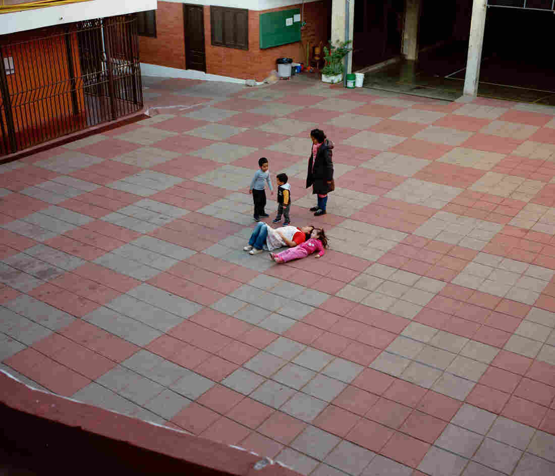Kids play and lay on the ground in a courtyard.