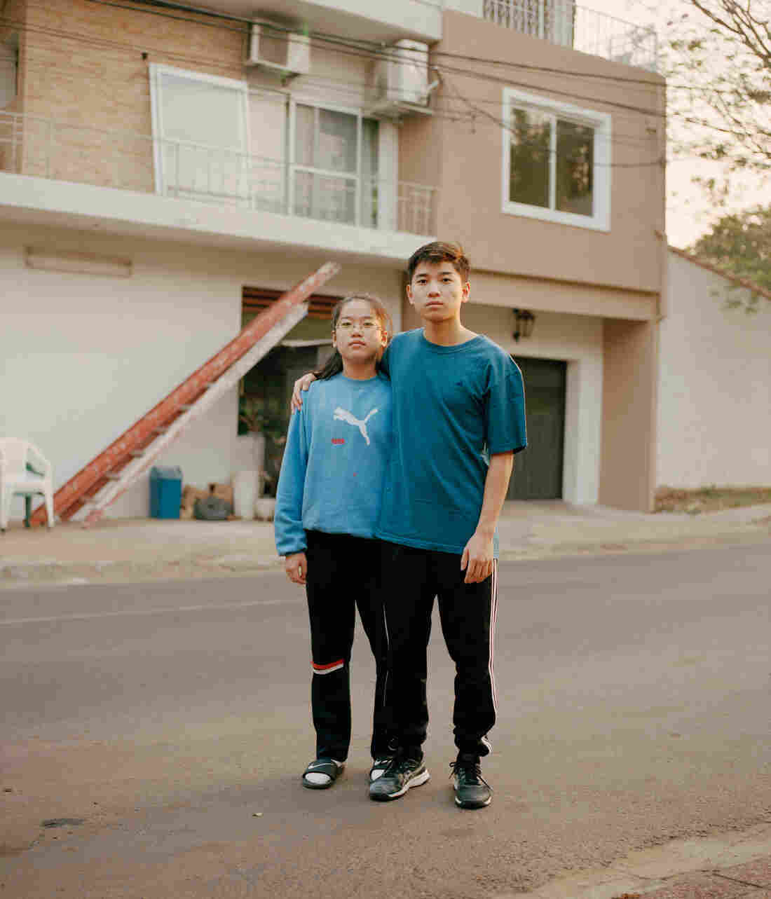 Siblings stand in the street and put an arm around each other.