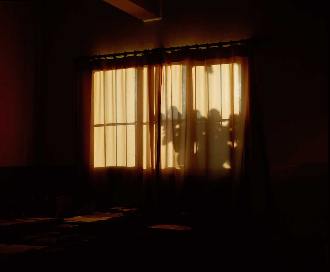 A curtain covers a window at sunset.