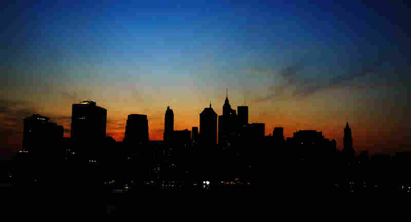 The sun sets over the dark Manhattan skyline on August 14, 2003. A power outage affected large parts of the northeastern United States and Canada.