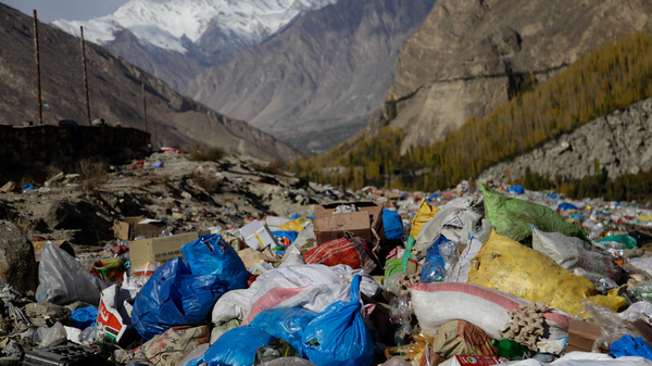 Trash from an informal dump in far northern Pakistan is frequently incinerated, sending up plumes of foul-smelling smoke right near a glacial lake frequented by tourists.