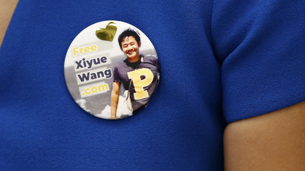 Hua Qu, the wife of Xiyue Wang, a Princeton University graduate student being held at an Iranian prison, wears a button bearing a picture of her husband as she speaks at a news conference to mark the third anniversary of his imprisonment, Aug. 8, 2019, in Washington, D.C.