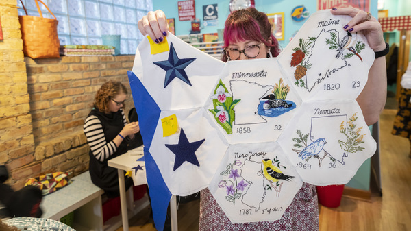Jenni Grover holds a collection of finished patches from a quilt created by more than 100 volunteers across the country. The plans for the quilt were discovered at the estate sale of 99-year-old Rita Smith, who died earlier this year. Several dozen volunteers gathered to help put the pieces together at the Wishcraft Workshop in Chicago on Dec. 7.