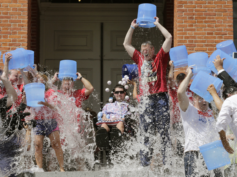 Pete Frates, (seated, center) participates in the Ice Bucket Challenge with Massachusetts Gov. Charlie Baker to raise money for ALS research at the Statehouse in Boston in 2015. (Charles Krupa/AP)