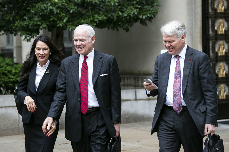 Attorney Charles Cooper, representing former national security aide Charles Kupperman (center) departs federal court in Washington in October. On Tuesday, Cooper asked a federal court to keep alive a lawsuit centered on a now-withdrawn subpoena filed by House Democrats that sought Kupperman's testimony as part of the impeachment inquiry. (Bloomberg via Getty Images)
