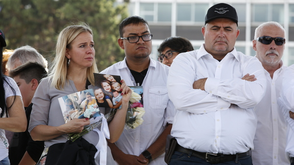 Adriana Jones, a member of the LeBaron family, holds images of relatives who were killed in November. Jones and other family members were participating in a Dec. 1 protest in Mexico City against Mexican President Andrés Manuel López Obrador to express anger and frustration over increasingly appalling incidents of violence.
