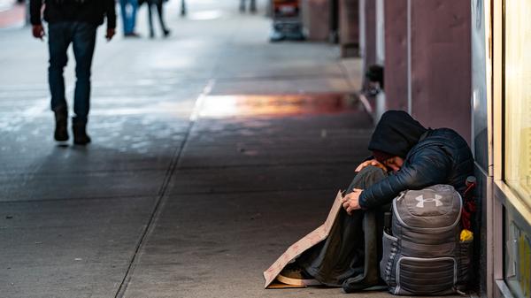 A person sleeps on a sidewalk near New York