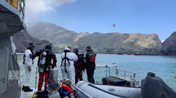 Divers near White Island search for a body in the water on Saturday after the volcanic eruption earlier this week.