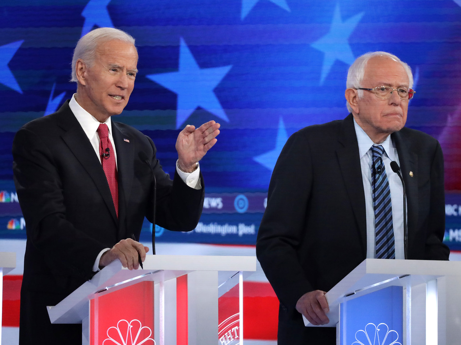 Former Vice President Joe Biden (left) and Sen. Bernie Sanders lead the crowded Democratic presidential primary field, according to the latest NPR/<em>PBS NewsHour/</em>Marist Poll. Above, they appear during the Democratic presidential primary debate in Atlanta on Nov. 20. (Alex Wong/Getty Images)