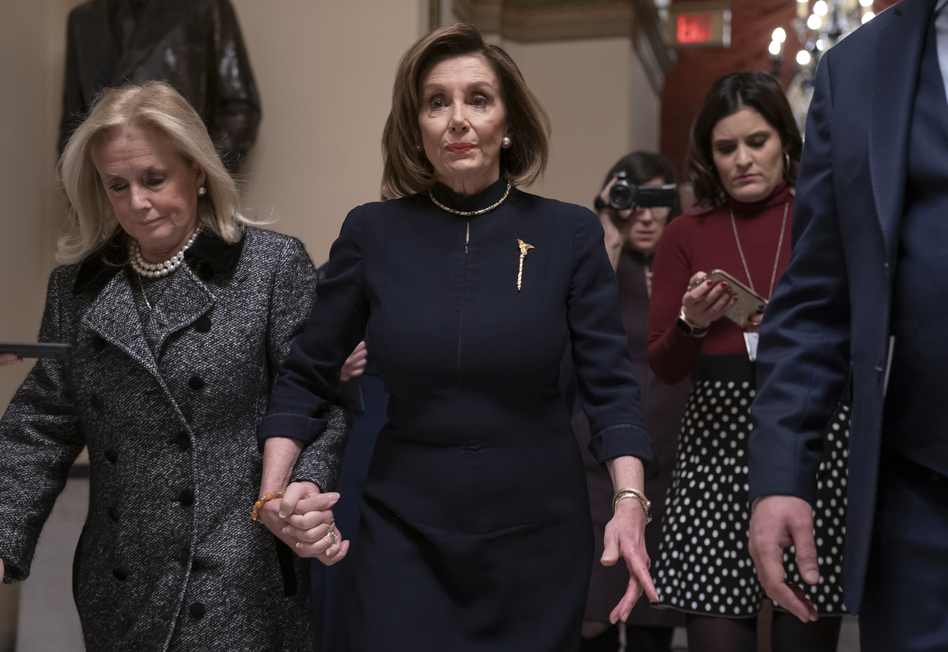 House Speaker Nancy Pelosi, D-Calif., holds hands with Rep. Debbie Dingell, D-Mich., as they walk to the chamber where the House begins debate on the impeachment charges against President Trump. (J. Scott Applewhite/AP)