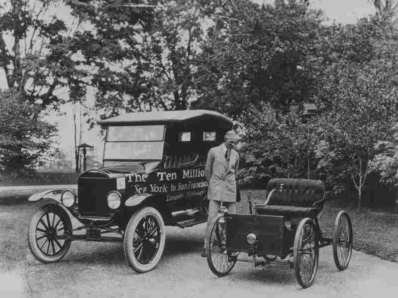 American motor vehicle industry pioneer Henry Ford (1863 - 1947) standing next to the first and the ten millionth Model-T Ford. Ford was able to mass produce the Model-T and have increasing profits year after year, despite not raising prices drastically.